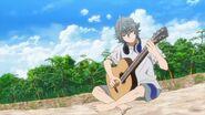 Sosuke playing the guitar on the beach
