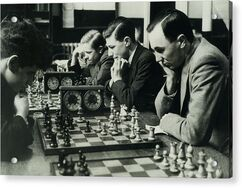 Black and white image of white men playing chess.
