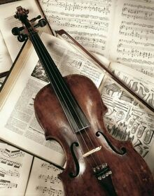 A violin rests on a bed of open faced books featuring sheets of music.