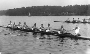 Black and white image of a regatta. The boat in frame holds eight rowers and one coxswain. The regatta is taking place in front of a tree filled landscape