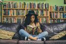Girl in hat reading on couch