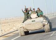 Iraqi military men riding on tank.jpg