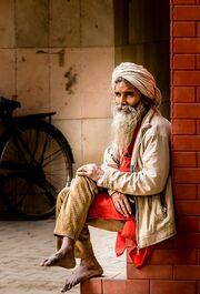 Indai ember ül az utcán, viseletes európai ruhában.