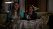 Kara e Alex vendo uma falsa Supergirl na TV