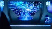 Brainiac's ship charging towards a wormhole