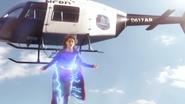 Supergirl protegendo um helicóptero da polícia