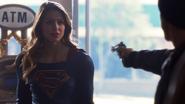 Supergirl conversando com um assaltante