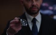 Lex Luthor holding a transmatter portal watch