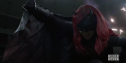 Batwoman covers herself from Crow bullets.png