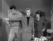 A black and white screenshot from the television series, The Beverly Hillbillies shows Max Baer Jr. as Jethro, Nancy Kulp as Jane Hathaway and Sharon Tate as Janet Trego, a secretary. Tate is wearing a business suit and a dark wig and is watching Miss Hathaway