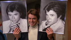 Tab E1 - Paul holding photos of himself.png