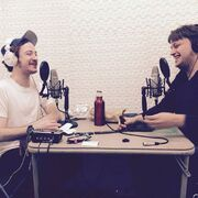 Griffin and David smiling and sitting across from one another, each wearing headphones and sitting in front of a microphone.