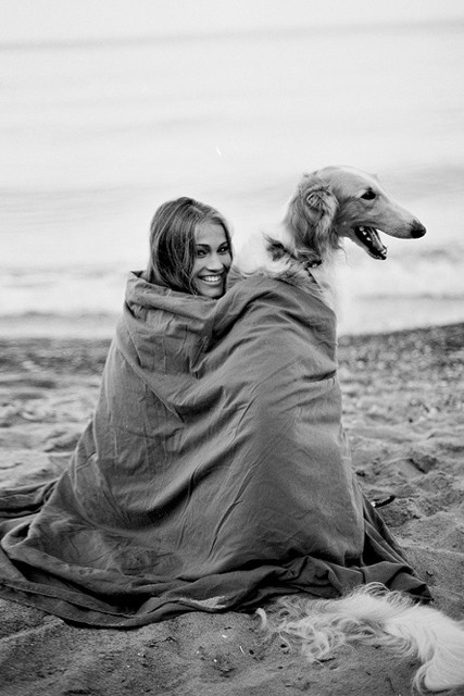 A girl and long haired dog wrapped up in a blanket on the beach.jpg