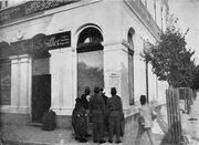 """Photo of large white building with one signs saying """"Moritz Schiller"""" and another in Arabic; in front is a cluster of people looking at poster on the wall."""