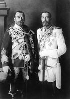 Two bearded men of identical height wear military dress uniforms emblazoned with medals and stand side-by-side