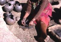 Mujer zulú, amasando los colombines con hollín.