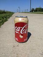 12oz Vanilla Coke on smooth sidewalk