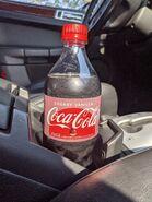 Cherry Vanilla Coke bottle in a drink holder in a car