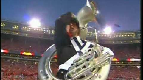 Tuba player hits camera man with tuba