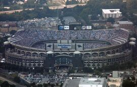 Aerial shot of an open-air stadium during a football game. The outside facing is defined by a series of arches, and scoreboards are visible at the top of the facility.