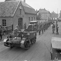 595px-A Bren Gun Carrier brings in a batch of German prisoners