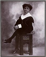 A black-and-white photograph of a curly-haired young boy, seated with one leg crossed over the other, and wearing a sailor suit.
