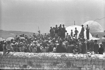 WORSHIPPERS STANDING ON THE ROOF OF ONE OF THE BUILDINGS AT THE TOMB OF RABBI SHIMON BAR YOHAI DURING THE CELEBRATIONS OF THE LAG B'OMER HOLIDAY. חג (1)