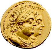 """A gold coin shows paired, profiled busts of a plump man and woman. The man is in front and wears a diadem and drapery. It is inscribed """"ΑΔΕΛΦΩΝ""""."""