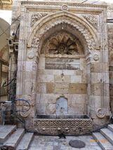 סולימאן שממול לשער השלשלת מבחוץ. סרקופג מעוטר משמש כשוקת