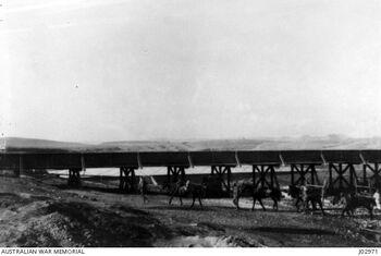 A MILITARY RAILWAY BRIDGE OVER THE WADI GHUZZE, IN PALESTINE. BEYOND THE BRIDGE IS SEEN A DAM מסילת הרכבת מרפיח לבאר שבע - גשר העץ מעל נחל הבשור