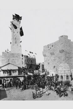VIEW OF JAFFA GATE IN JERUSALEM WITH TURKISH FLAGS DURING THE OTTOMAN RULE IN PALESTINE. IN THE PHOTO, PEOPLE CARRYING FLAGS AND SIGNS HONORING THE TU