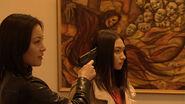Naomi holding Shiori at gunpoint