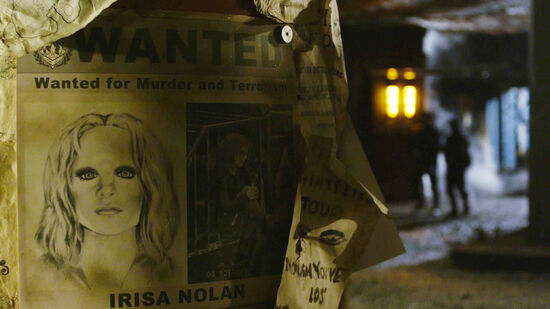 """a wanted poster hung on a post stating """"Wanted for Murder and Terrorism"""" above a drawing and photo of Irisa and her name """"Irisa Nolan"""" written below her pictures"""