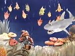 Bad Polly in the ocean with fishes, clams, oysters, and a shark in Muppet Treasure Island Sing-Alongs