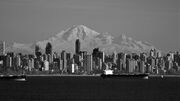 Black and white picture of the downtown Vancouver cityscape, a mountain in seen in the background.