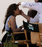 """A side-view shot of a female teenager with long brown hair who smiles as a woman with dark brown hair, glasses, and a white shirt bends to brush the teen's face with make-up. The teen sits in a chair. Beside her is an identical chair with its back facing the camera; the chair's back has the words """"The Last Song"""" written across it."""