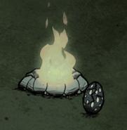 Pęknięte Jajo Wysokiego Ptaka tuż przy ogniu w czasie nocy