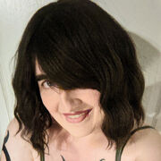A picture of a smiling woman with brown hair, pale skin, and visible tattoos. She is wearing a tank top with bare shoulders and appears to be looking at the camera.
