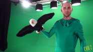 Nice Peter Holding Eagle Puppet in a Green Suit