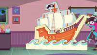 Pirate Pinkie pushing a cardboard pirate ship stand EGDS3