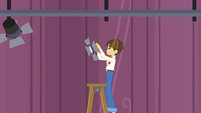 Techie kid hanging a floodlight EG