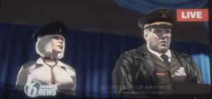 Hilde obok Generała Hemlocka na ekranie telewizyjnym