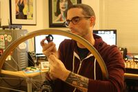 Josh Sawyer removing spokes from a bicycle wheel