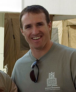 A man is smiling. He is wearing a gray T-shirt with a pair of black sunglasses hanging from the collar.