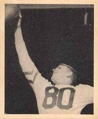 Black and white photograph of Armstong in a light-colored number 80 jersey reaching up with his right hand to catch a football