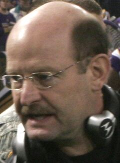 Head shot of bald white man (Brad Childress) with headset