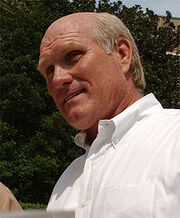 A balding man, who is wearing a white shirt.