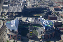 Two stadiums in an industrial area. Both have roofs with large arched trusses.
