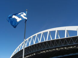 A blue flag with a white number 12 flies against a clear sky. An expansive white roof truss is behind the flagpole.