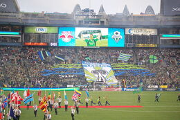 A stand of a stadium with fans holding a large banner depicting the Space Needle. Green and blue flags wave throughout the stand and the flags of different nations are held by people on the field.